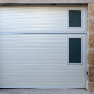 Porta basculant motoritzada d'obertura interior amb panell aïllat i vidre laminat