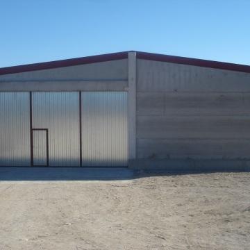 Porta corredera de grans dimensions amb xapa salve i portella d'accés
